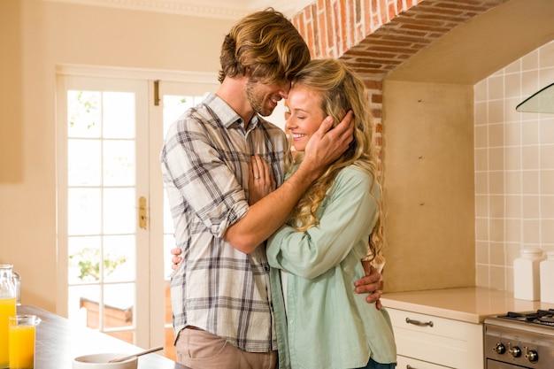 かわいいカップルが台所で寄り添う