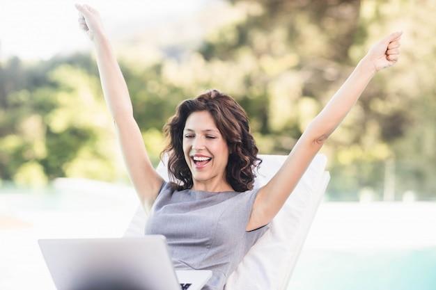 ラップトップを使用してプールサイドのサンラウンジャーの近くに興奮している若い女性