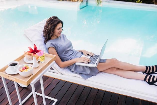 サンラウンジャーでリラックスしながらプールサイドの近くのラップトップを使用して若い女性
