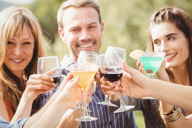 スイミングプールで飲み物を楽しんでいると休日を楽しんで幸せな若い友達