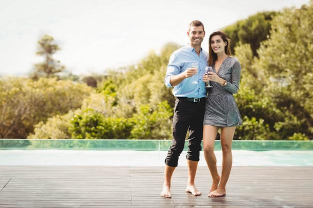 リゾートでプールサイドの近くの飲み物を楽しむ若いカップル