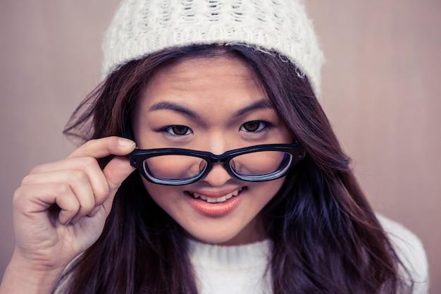 Улыбается азиатская женщина, держащая очки и смотрящая на камеру