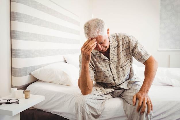 Разочарованный старший мужчина сидит на кровати в спальне