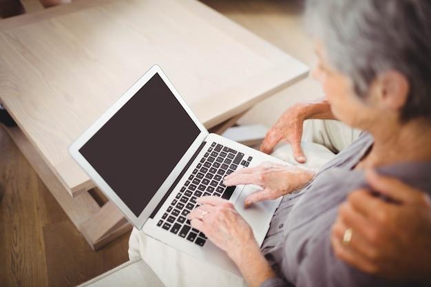 年配の女性がソファーに座っているとリビングルームでラップトップを使用して