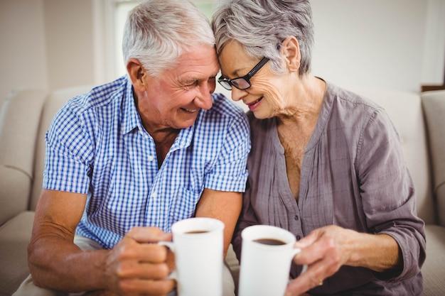 ソファに座っているとリビングルームでコーヒーを飲んでいる年配のカップル