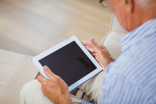年配の男性がソファーに座っていたとリビングルームでデジタルタブレットを使用して