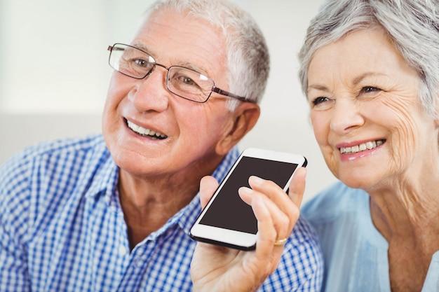 携帯電話で話しながら笑っている年配のカップル