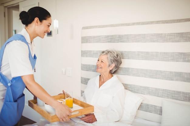 看護師の寝室で年配の女性に朝食を提供