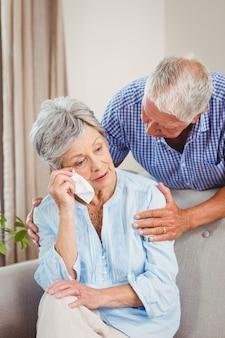 年配の男性がリビングルームで動揺の年配の女性と話しています。