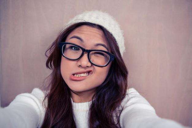Азиатская женщина делает лица и смотрит в камеру