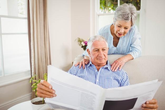 年配の女性がリビングルームで新聞を読んで年配の男性人に話しています。