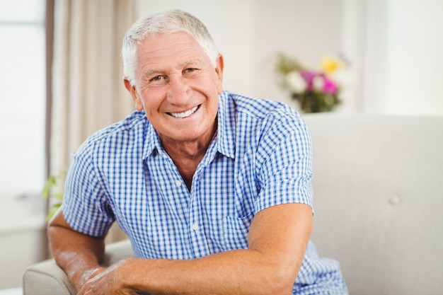 年配の男性人のカメラ目線とリビングルームで笑顔