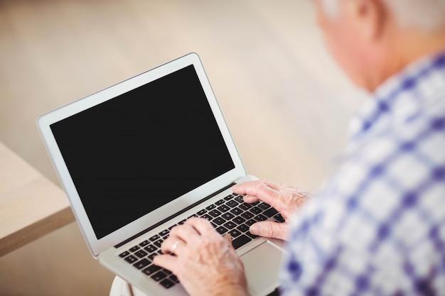 年配の男性人のソファーに座っているとリビングルームでラップトップを使用して