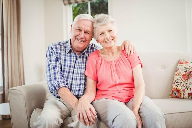 ソファに座っているとリビングルームで笑顔の年配のカップルの肖像画