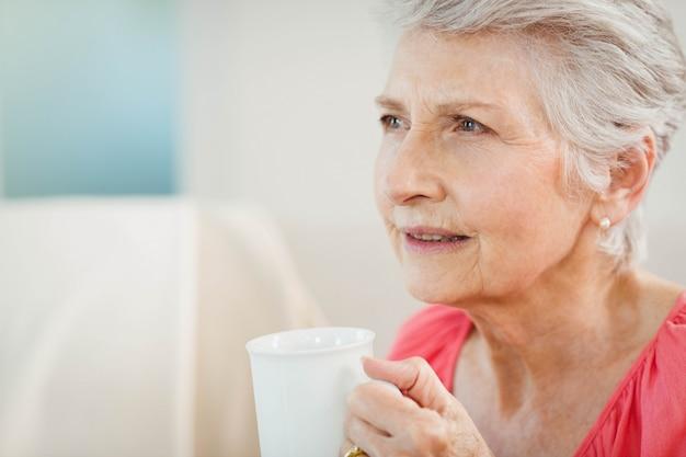 年配の女性が自宅でコーヒーを飲む