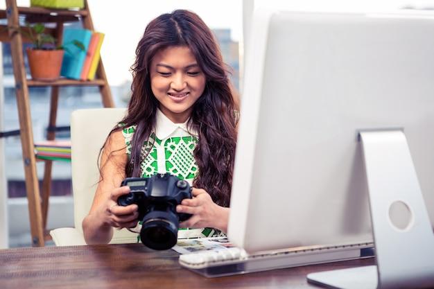 オフィスでカメラを持って笑顔の創造的な実業家