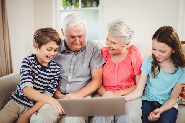 年配のカップルと彼らの壮大な子供たちが居間でラップトップを使用して