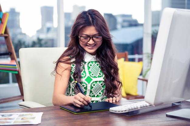 オフィスでデジタルボードを使用して笑顔の創造的な実業家