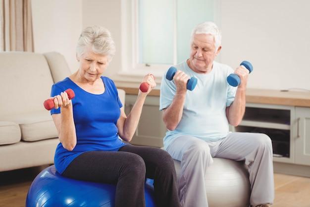 年配のカップルが自宅でエクササイズボールに座りながらダンベルを持ち上げる