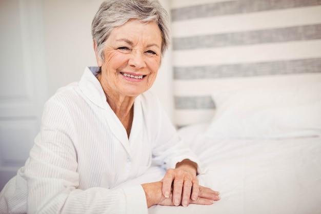 年配の女性がベッドの上に座っている間笑みを浮かべての肖像画