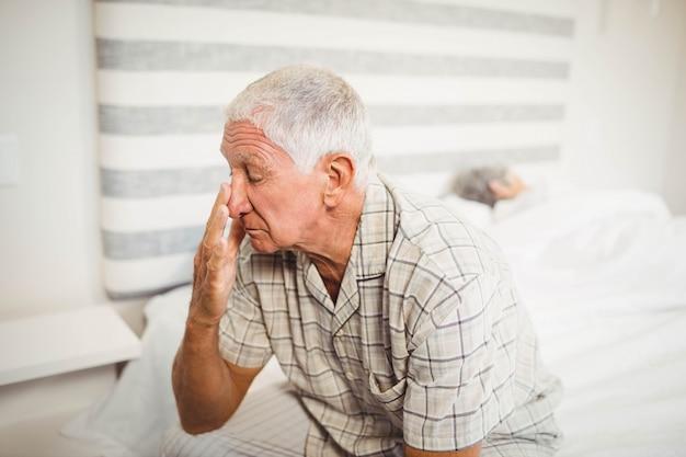 年配の男性人の寝室でベッドの上に座って