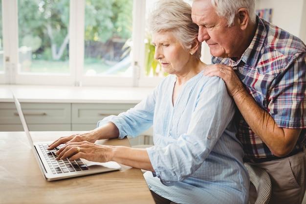 年配のカップルが自宅でラップトップを使用して