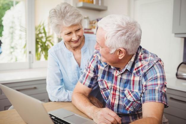 自宅でラップトップを使用しながら話している年配のカップル