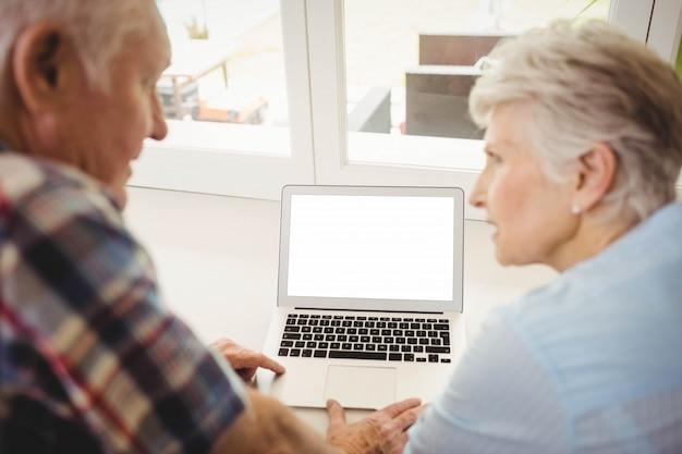 年配のカップルが自宅でラップトップを使用しながら互いに話しています。