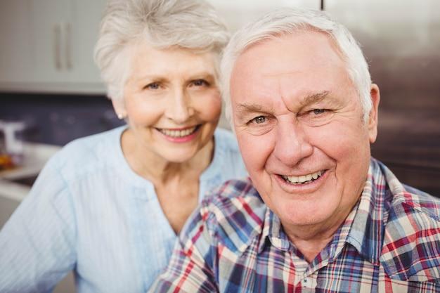 自宅で笑顔の年配のカップルの肖像画