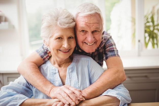 自宅で抱きしめる年配のカップルの肖像画