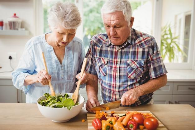 年配のカップルが台所でサラダを準備します。
