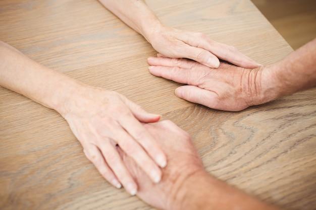 テーブルの上に手を繋いでいる年配のカップル