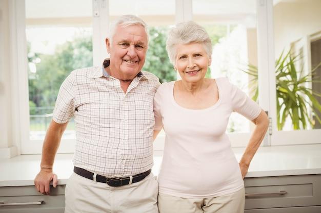 笑みを浮かべて、自宅の台所に立っている年配のカップルの肖像画