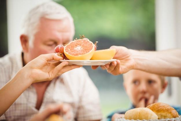 自宅で朝食をとりながらフルーツのプレートを渡す手のクローズアップ
