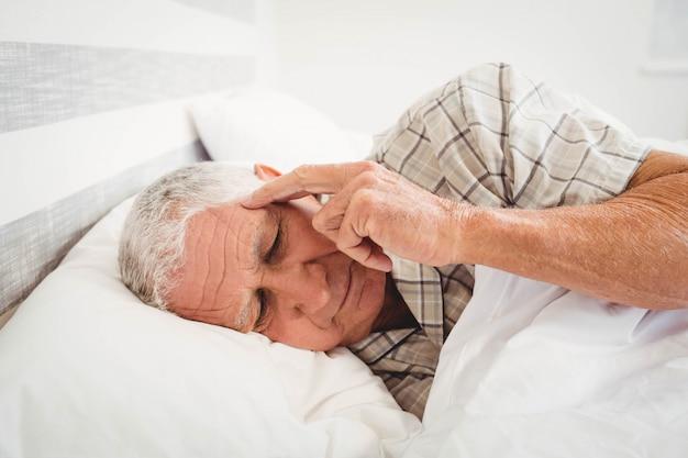 Разочарованный старший мужчина лежал на кровати в спальне