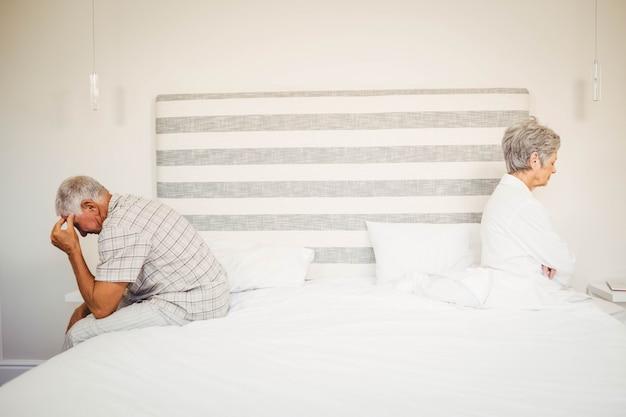 戦いの後ベッドの反対側に座っている動揺の年配のカップル