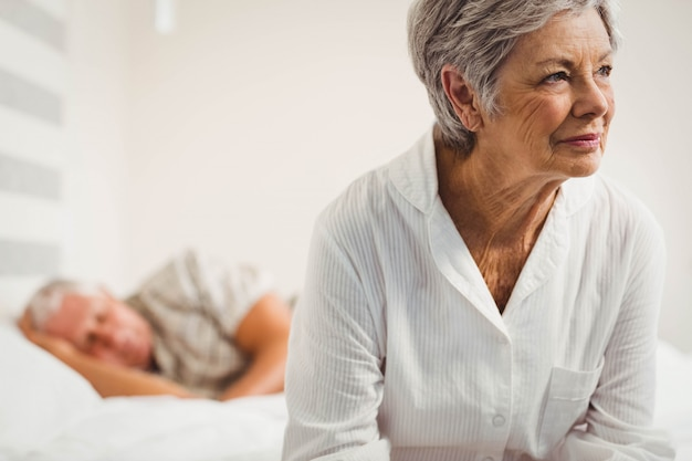 寝室のベッドの上に座って心配している年配の女性