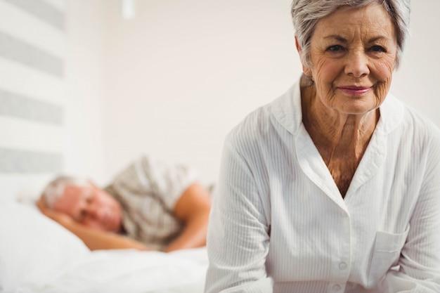 寝室のベッドの上に座っている年配の女性