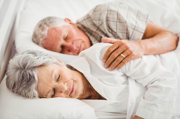 寝室のベッドで寝ている年配のカップル