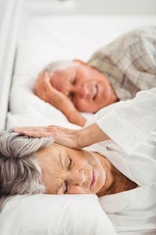 年配の女性がベッドでいびきをかく人の耳を覆う