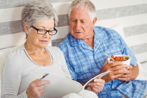 寝室で朝食をとりながら雑誌を読んで年配のカップル