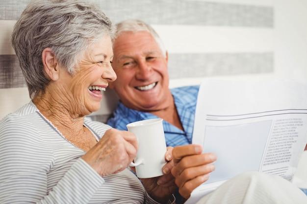 Пожилая пара смеется, читая газету в спальне