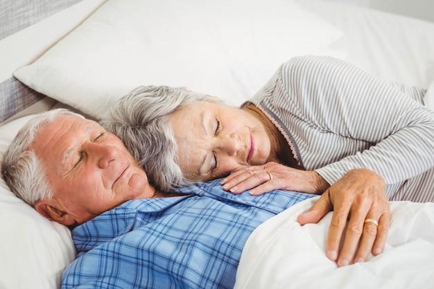 Пожилая пара спит на кровати в спальне