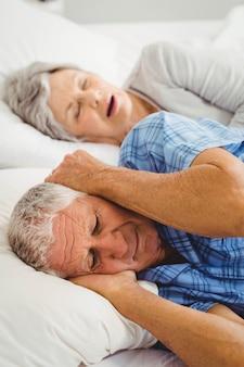 女性がベッドでいびきをかく間彼女の耳を覆う年配の男性