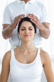 妊娠中の女性が自宅でマッサージ師からヘッドマッサージを受ける