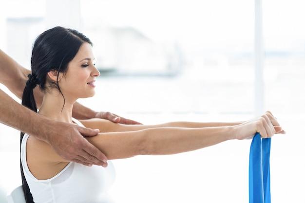 Врач осматривает и дает физиотерапию беременной женщине на тренировочном мяче
