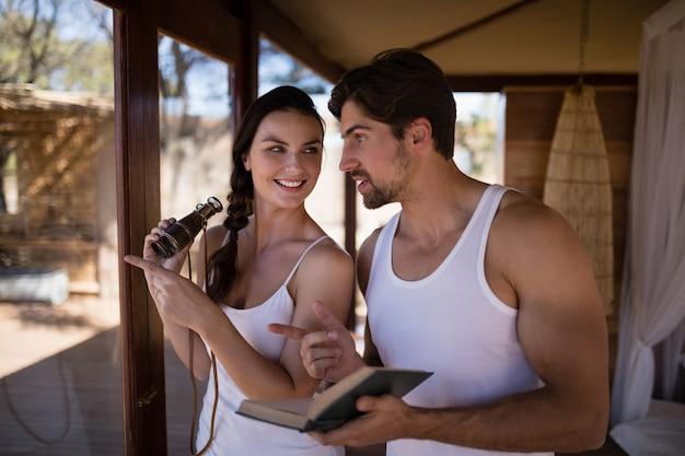 Пары держа бинокль пока читающ роман во время каникул сафари