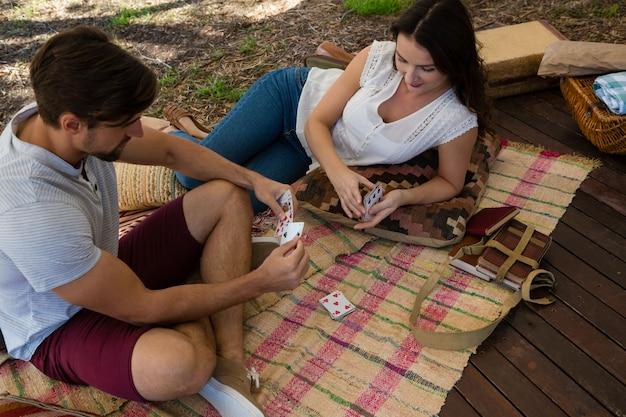 Пара играет в карты на доске