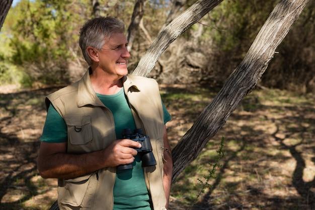 Мужчина держит бинокль в лесу