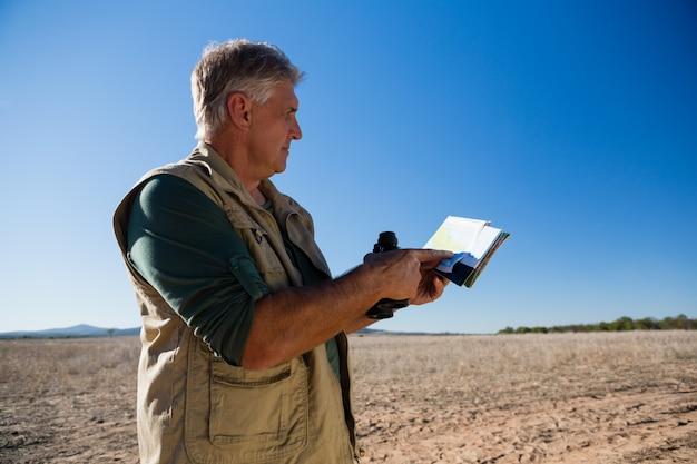 Мужчина держит карту и бинокль на ландшафте